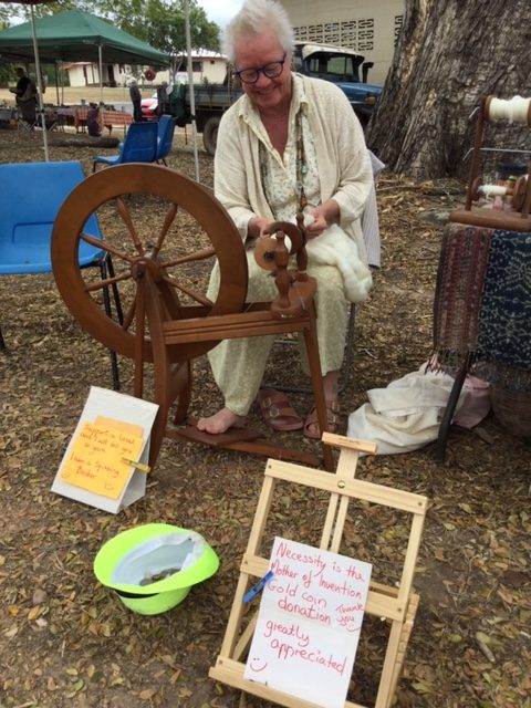 TRACQS Community Development Program participant, Ulla happily spinning her own yarn at a market.